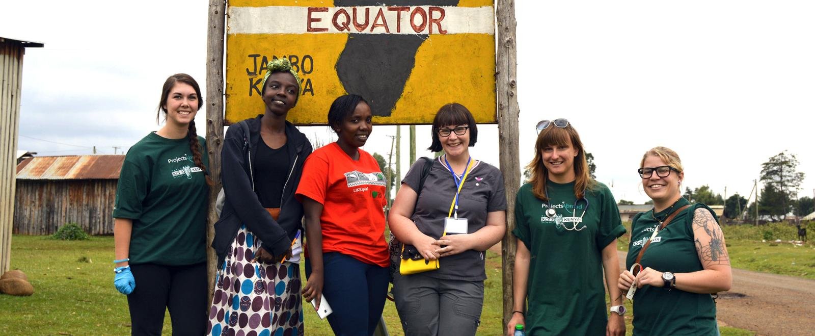 Projects Abroad Kenya staff members and Medicine and Healthcare volunteers from the United States, Ireland, Germany and Canada pose next to an 'Equator' sign in Nanyuki, Kenya